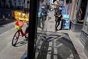 A discarded Lime rental bike stands in a bus shelter as a Londoner wearing a face covering passes-by during the third lockdown of the Coronavirus pandemic, on 29th March 2021, in London, England.