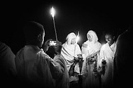 Pilgrims and priests celebrate Ethiopian Orthodox Christmas in Lalibela, Ethiopia beside centuries-old churches hewn from the rock.