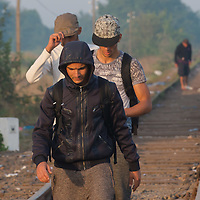 Illegal migrants cross the border between Hungary and Serbia walking on railway tracks leading through an opening on the border fence near Roszke (about 174 km South of capital city Budapest), Hungary on August 30, 2015. ATTILA VOLGYI