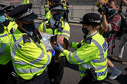 © Licensed to London News Pictures. 01/09/2020. London, UK. Police arrest a member of the Extinction Rebellion (XR) environmental campaign group as they gather in central London to blockade Parliament. XR plan to peacefully disrupt the UK Parliament with actions planned over two weeks, until MPs back the Climate and Ecological Emergency Bill and prepare for crisis with a National Citizens' Assembly. Photo credit: Rob Pinney/LNP