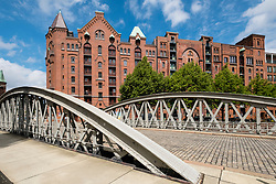 View of historic red brick warehouses and bridge at Speicherstadt beside canals in Hamburg Germany