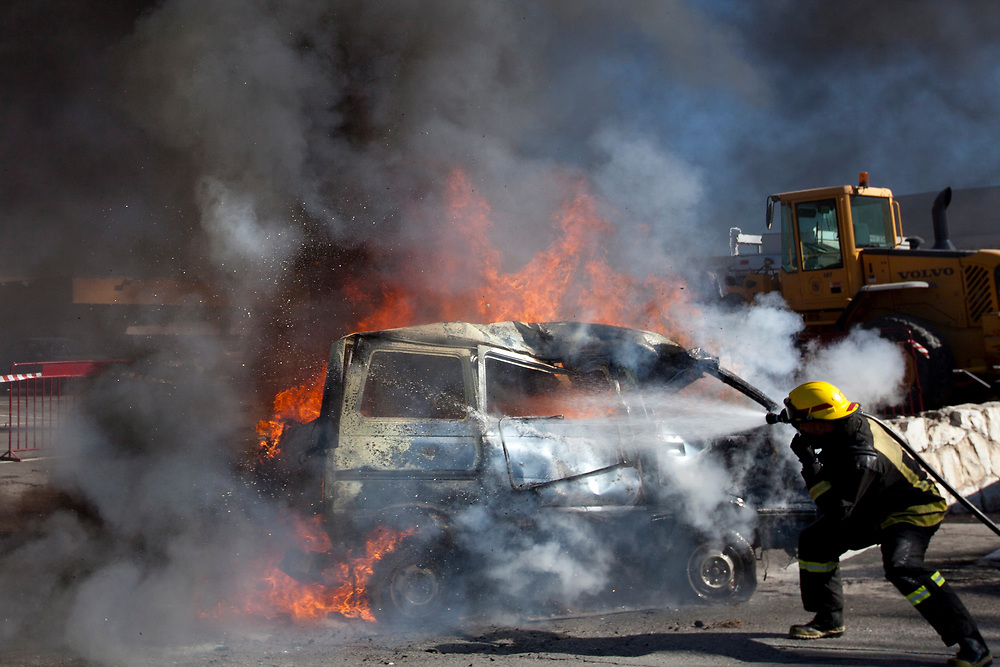 An Israeli fire-fighter extinguishes a burning car, simulating a car bombing at a city emergency service and distribution center, as part of a day-long war drill in Jerusalem on November 30, 2010.