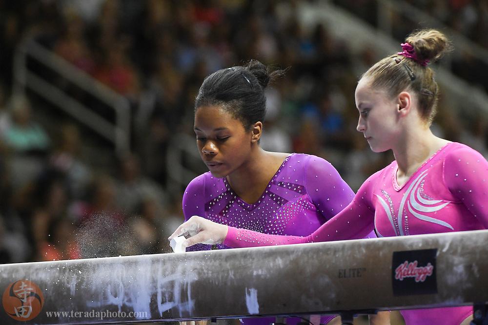 July 8, 2016; San Jose, CA, USA; Gabby Douglas (left), from Tarzana, CA, blows chalk as Rachel Gowey (right), from Urbandale, IA, applies chalk during the balance beam in the women's gymnastics U.S. Olympic team trials at SAP Center.