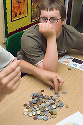 Boy with learning disability sitting at desk in classroom working on maths problem,
