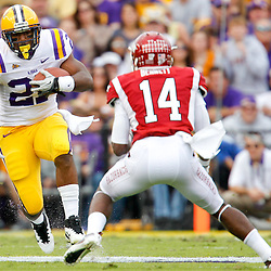 November 25, 2011; Baton Rouge, LA, USA; LSU Tigers running back Kenny Hilliard (27) is pursued by Arkansas Razorbacks safety Eric Bennett (14) during the second quarter of a game at Tiger Stadium.  Mandatory Credit: Derick E. Hingle-US PRESSWIRE