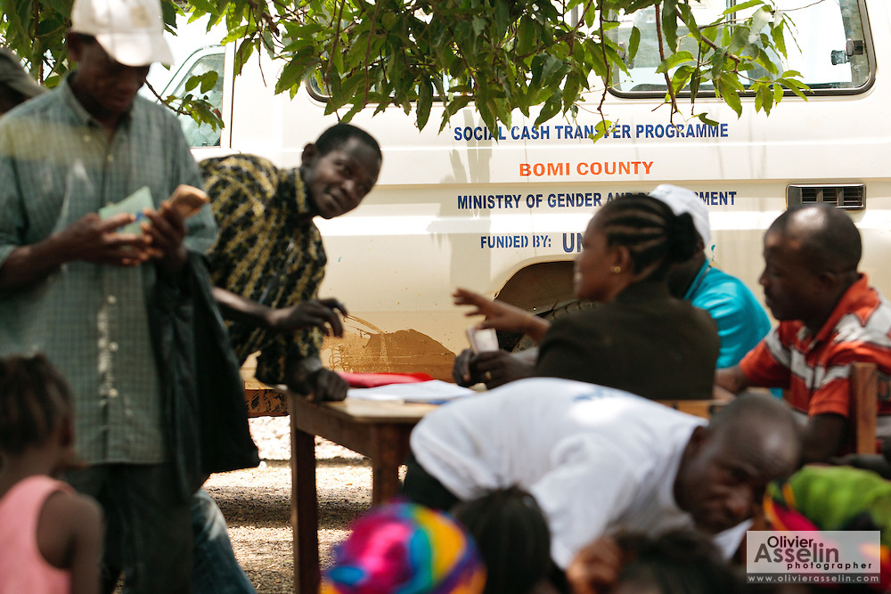 Money is handed out to beneficiaries during a UNICEF-sponsored social cash transfer programme distrubution in the village of Julijuah, Bomi county, Liberia on Tuesday April 3, 2012. Beneficiary households receive monthly transfers that vary according to the size of the household, with additional sums provided for each child enrolled in school. Families are selected for participation in the programme based on two key criteria: they must be both extremely poor and labour-constrained.