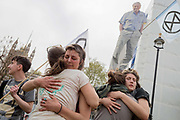 Campaigners hug beneath an image of veteran wildlife and environmental broadcaster Sir David Attenborough is held high in Parliament Square during the week-long protest by climate change activists with Extinction Rebellions campaign to block road junctions and bridges around the capital, on 23rd April 2019, in London England.