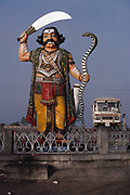 Statue of a warrior with a raised sword in one hand and a cobra in the other; and a bus, Mysore, South India.