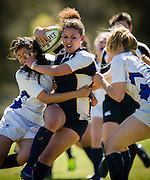 Angelita Priscilla Ochoa, center, of University of California San Diego fights off defenders from the University of California Santa Barbara during a women's rugby match at UCSD on March 4, 2012.