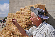 Bales of straw in storage in a dairy farm. Photographed at Kibbutz Harduf, Galilee, Israel. A farmer is inspecting the straw