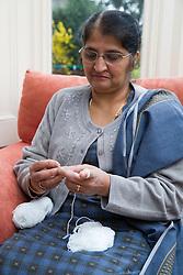 Older woman at home sitting knitting,