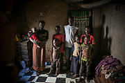 Akol Harriet, about 34, at left holding a baby, stands with seven of her eight children in her home in Gulu. Harriet was abducted by LRA at the age of eight in Wiiagwem village in Lira District, and spent 13 years in the bush as a girl soldier and sex slave. she said her husband, a captain in charge, had four wives. She gave birth to two children in the bush and later had six more from the new husband. The new husband rarely stays with her. She sells boiled corns to support herself and children.