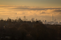 """The first rays of the sun illuminate Londons skyscrapers and clouds to the south of the city. The threatened snow from """"The Beast From The East"""" weather system doesn't materialise overnight in London leaving a crisp, clear morning, seen from Hampstead Heath in North London. London, February 27 2018."""