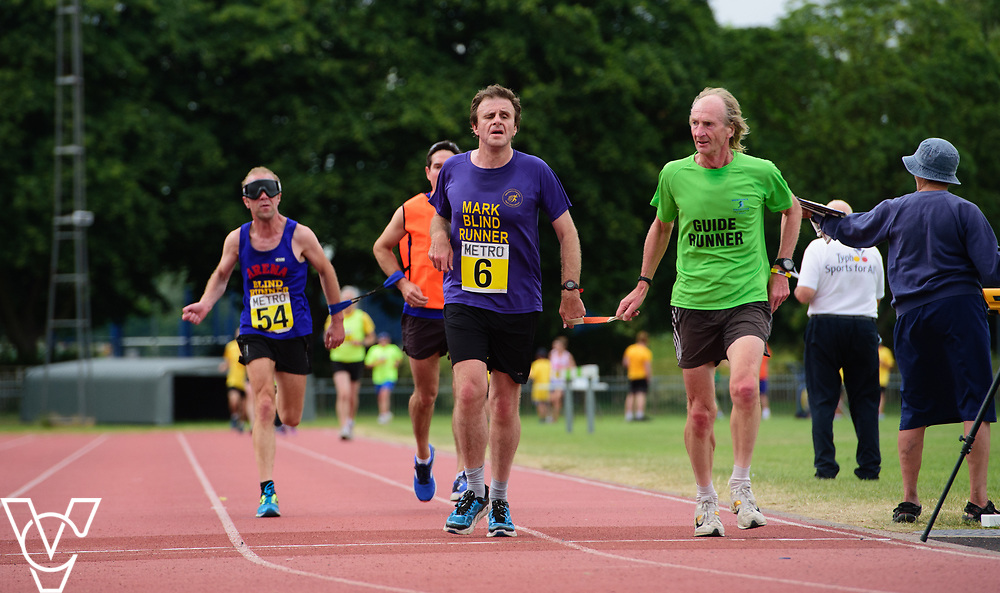 Event: 5000 meter relay<br /> Competitors, from left: Keith Turner and Mark Ellis<br /> <br /> Metro Blind Sport's 42nd Athletics Open, held at Mile End Stadium, Tower Hamlets, London.<br /> <br /> Picture: Chris Vaughan Photography for Metro Blind Sports<br /> Date: June 16, 2018