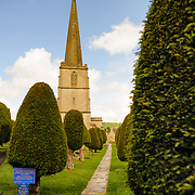 Walkway through the Yew trees and steeple at the Parish Church of St Mary in Painswick, Gloucestershire, in England's Cotswolds region.