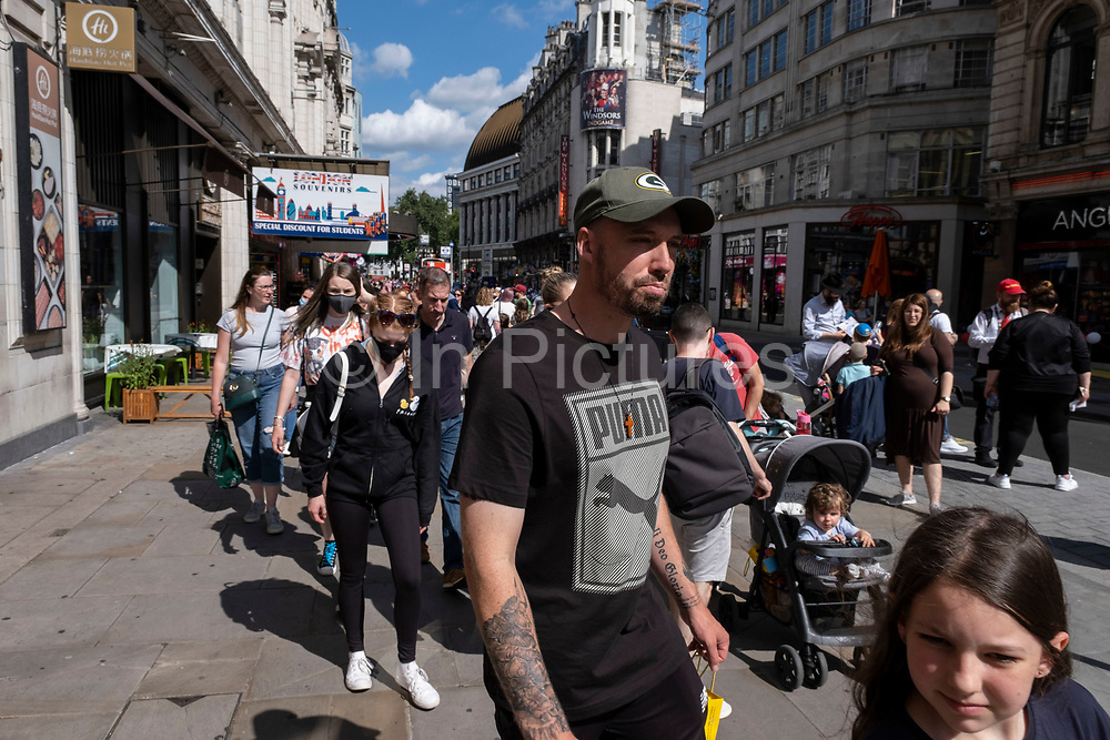 With many people and families staying in the UK for their Summer break during the school holidays, a large number of domestic tourists, who may normally have been travelling abroad, have decended on the capital to see the sights, as seen here in Piccadilly on 10th August 2021 in London, United Kingdom. Following the Coronavirus / Covid-19 health scare of the last two years, and with some travel restrictions still in place, more people have chosen a staycation which is a holiday spent in ones home country rather than abroad, or one spent at home and involving day trips to local attractions.