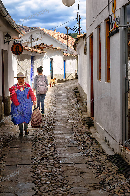Narrow cobblestone streets and quechua natives in Cusco