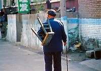 China, Taiyuan, 2008. On his way to watch a Chinese opera performance outside, an old man carries everything he needs..