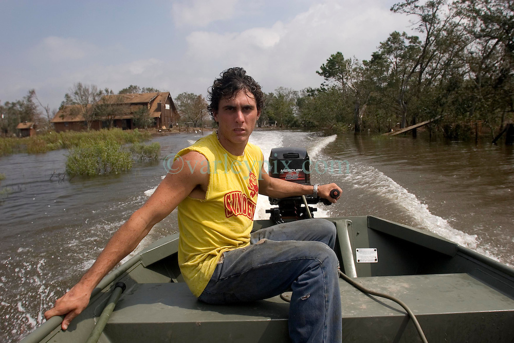 25 Sept, 2005.  Carlyss, Louisiana.  Hurricane Rita aftermath. <br />  Local cajun man Josh Herman tours the swamps and bayou's checking on neighbours and their homes. He also removed perishable items from his father's convenience store to place in a freezer run by a generator nearby.<br /> Photo; ©Charlie Varley/varleypix.com