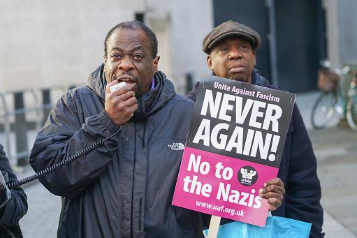 A protester holds a sign reading 'Never again! No to the Nazis' as United Against Fascism supporters protest against BBC for interviewing French far-right leader Marine Le Pen on the BBC's 'Andrew Marr Show on Remembrance Sunday, November 13, 2016.<br /> <br /> https://www.prospectmagazine.co.uk/world/watching-the-world-fall-apart-marine-le-pen-andrew-marr