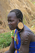 Mursi Tribe in The Omom River Valley, Ethiopia. A young tribeswoman with beauty scarring, The Mursi tribe is a nomadic cattle herder ethnic group located in Southern Ethiopia, close to the Sudanese border.