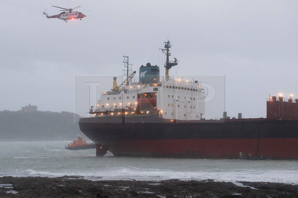 © Licensed to London News Pictures. 18/12/2018. Falmouth, UK. A rescue helicopter flies over Russian cargo ship Kuzuma Minin, run aground on the reef off Gyllyngvase beach in Falmouth Bay in the early hours this morning. The Falmouth lifeboat and the Coastguard helicopter are involved in the major incident.  Photo credit: Mark Hemsworth/LNP