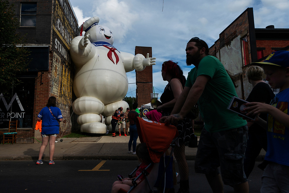 A large inflatable Stay Puft marshmallow man looms over main street as festival goers walk by at the annual Mothman festival in Point Pleasant, W.Va. on September 15, 2018.