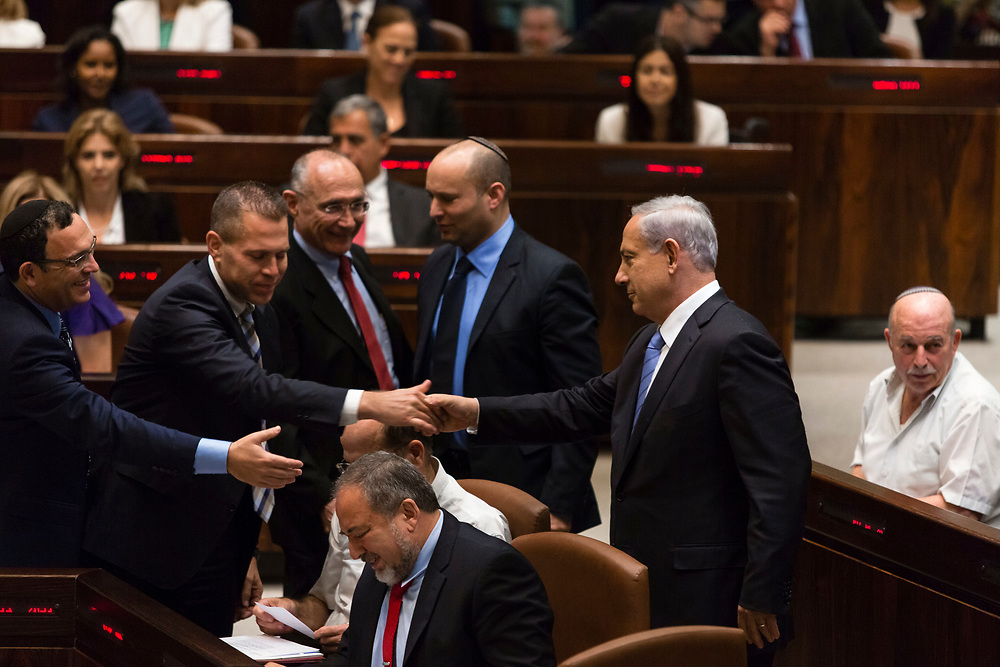 Israel's Prime Minister Benjamin Netanyahu (2nd R) is greeted by Israeli parliament members following his speech, during the winter session opening of the Knesset, Israel's parliament in Jerusalem, on October 27, 2014.
