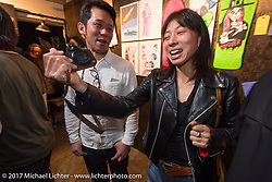 Journalists Tadashi Kono and Nozomi Fujimura at the Deus Ex Machina Harajuku store party before the 2017 Mooneyes Show. Tokyo, Japan. Friday December 1, 2017. Photography ©2017 Michael Lichter.