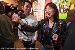 Journalists Tadashi Kono and Nozomi Fujimura at the Deus Ex Machina Harajuku store party before the 2017 Mooneyes Show. Tokyo, Japan. Friday December 1, 2017. Photography ©2017 Michael Lichter.