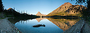 """Rising Wolf Mountain (9513 feet/2899 meters) and Sinopah Mountain (left) reflect in Pray Lake, in Glacier National Park, Montana, USA. Since 1932, Canada and USA have shared Waterton-Glacier International Peace Park, which UNESCO declared a World Heritage Site (1995) containing two Biosphere Reserves (1976). Rocks in the park are primarily sedimentary layers deposited in shallow seas over 1.6 billion to 800 million years ago. During the tectonic formation of the Rocky Mountains 170 million years ago, the Lewis Overthrust displaced these old rocks over newer Cretaceous age rocks. Glaciers carved spectacular U-shaped valleys and pyramidal peaks as recently as the Last Glacial Maximum (the last """"Ice Age"""" 25,000 to 13,000 years ago). Of the 150 glaciers existing in the mid 1800s, only 25 active glaciers remain in the park as of 2010, and all may disappear by 2020, say climate scientists. (Panorama stitched from 10 overlapping images.)"""