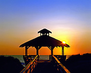 Silhouette of a gazebo among the sand dunes with the ocean in the background.