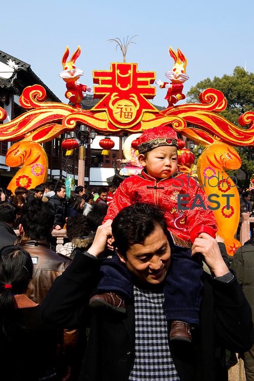 A man carries a baby on his shoulders, probably an only child, product of China's one-child policy, which produced generations nicknamed 'little emperors', during Chinese New year and the Festival of Lanterns at Yu Gardens, Shanghai, China, on February 4, 2011. Photo by Lucas Schifres/Pictobank