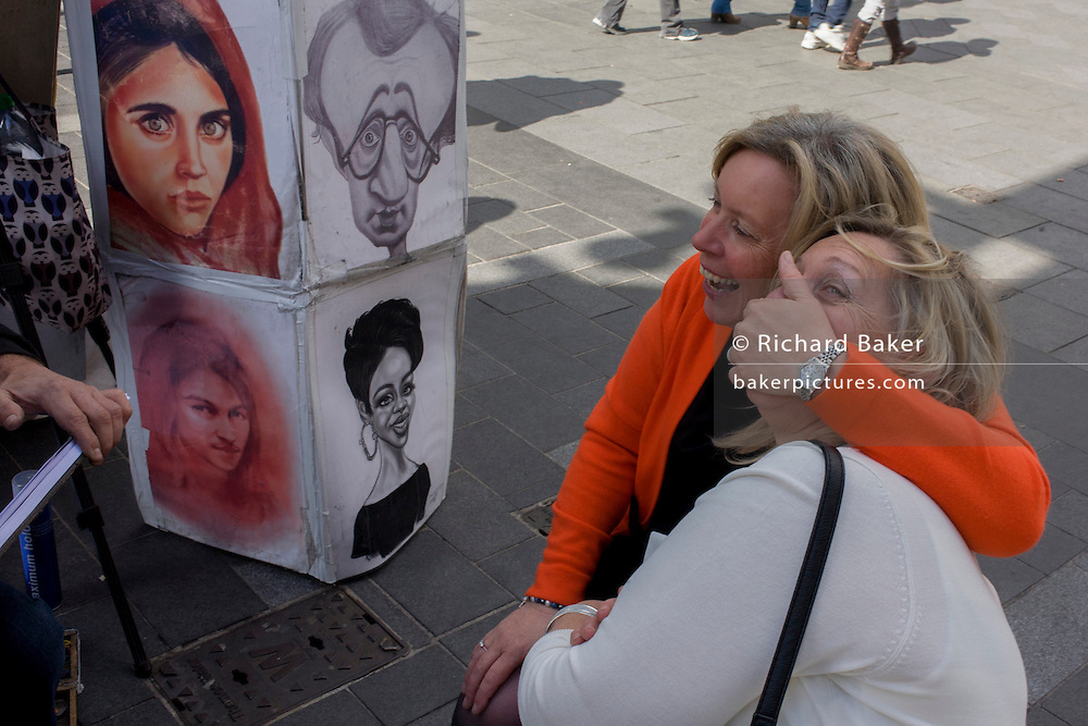 Two women mess about while having their portrait sketched by a street artist in Leicester Square