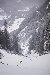 Man skiing downhill on snow