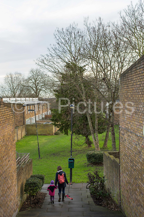 A mother and daughter walk hand in hand through Cressingham Gardens Estate on 9th January 2015 in South London, United Kingdom. Cressingham Gardens is a council garden estate, located on the southern edge of Brockwell Park. It comprises of 306 dwellings and built to the design of Lambeth Borough Council architect Edward Hollamby in the early 1970s. In 2012, Lambeth Council proposed regeneration of the estate, a decision highly opposed by many residents. Since the announcement, the highly motivated campaign group Save Cressingham Gardens has been active.