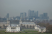 London, UK. Wednesday 2nd April 2014. Industrial pollution from Europe and dust from the Sahara region creates a layer of smog over the City of London. Barely visible through the poplluted air, the buildings seem to disappear into the poor air quality. View from Greenwich Park towards the skyline at Canary Wharf financial district across Greenwich Maritime Museum.