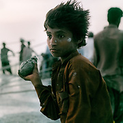 """A young pilgrim holds a coconut, to be thrown into the muddy crater for good luck. The steep trek to the rim of the highest volcano is the first ritual of the Hinglaj pilgrimage. Pilgrims come up to throw a coconut in the cold mud (to thank the gods for granting their wish) and to apply the holy mud to their faces etc. The area around Chandragup (meaning """"Moon Well""""), a sacred site to Hindu of 3 mud volcanoes (mainland Asia's largest ones)."""