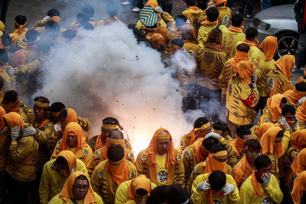 Firecrackers are let off insode a circle of temple officials during celebrations for the God Qingshan Wang.