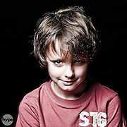 A portrait of a young boy with a mischievous smile, photographed in a studio against a black backdrop.