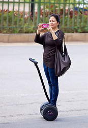 NANNING, CHINA - Monday, March 26, 2018: A local on a segway takes a photo of the Wales team during a team walk near the Wanda Realm Resort on day seven of the 2018 Gree China Cup International Football Championship ahead of the final against Uruguay. (Pic by David Rawcliffe/Propaganda)