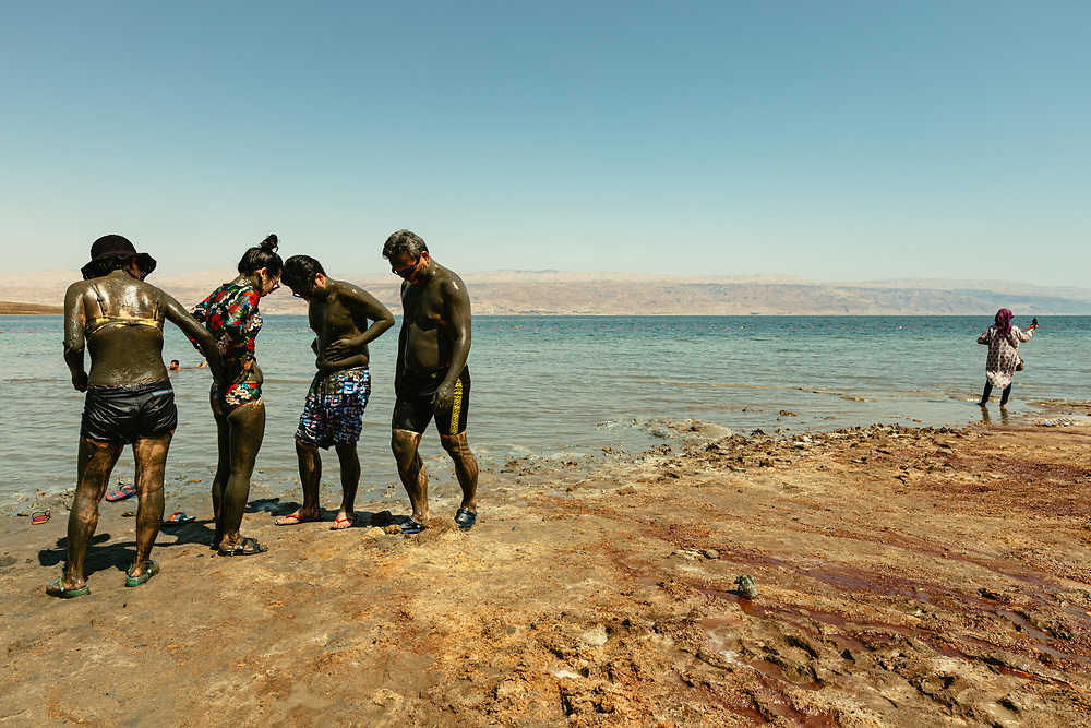 Tourists cover each other in mud on a hot summer day at Kalia Beach in the Dead Sea, Israel