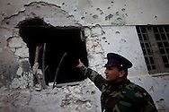 A protester dressed in army uniform points at a hole causesd by tank ammuniation  in Banghazi on Feb. 25, 2011.