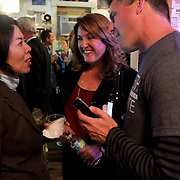 Yuna Shin, left, talks to Elizabeth Redenbaugh, center and her husband Jamie Redenbaugh at Ted's Fun on the River Tuesday November 4, 2014 for the election night results party of in Wilmington, N.C. (Jason A. Frizzelle)
