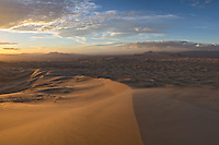 Strong winds blow sand across the Kelso Dunes as the sun sets. Located in the Mojave National Preserve, the Kelso Dunes are among the tallest in the country.<br /> <br /> Date Taken: 1/30/14