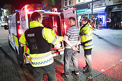© Licensed to London News Pictures . 27/12/2016 . Wigan , UK . Police cuff and detain a man . Revellers in Wigan enjoy Boxing Day drinks and clubbing in Wigan Wallgate . In recent years a tradition has been established in which people go out wearing fancy-dress costumes on Boxing Day night . Photo credit : Joel Goodman/LNP