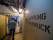 """Corridors with a few tons heavy doors out of steel inside the Honecker Bunker in Prenden. Inscription: Attention """"over pressure""""."""