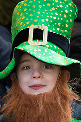 """London, March 13th 2016. The annual St Patrick's Day Parade takes place in the Capital with various groups from the Irish community as well as contingents from other ethnicities taking part in a procession from Green Park to Trafalgar Square.  PICTURED: A young """"leprechaun"""" watches the parade. ©Paul Davey<br /> FOR LICENCING CONTACT: Paul Davey +44 (0) 7966 016 296 paul@pauldaveycreative.co.uk"""