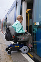 Woman wheelchair user boarding tram,
