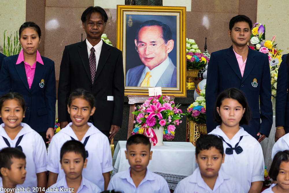 09 OCTOBER 2014 - BANGKOK, THAILAND: School children pose for pictures with a portrait of Bhumibol Adulyadej, the King of Thailand, during their visit to the hospital. The King has been hospitalized at Siriraj Hospital since Oct. 4 and underwent emergency gall bladder removal surgery Oct. 5. The King is also known as Rama IX, because he is the ninth monarch of the Chakri Dynasty. He has reigned since June 9, 1946 and is the world's longest-serving current head of state and the longest-reigning monarch in Thai history, serving for more than 68 years. He is revered by the Thai people and anytime he goes into the hospital thousands of people come to the hospital to sign get well cards.   PHOTO BY JACK KURTZ